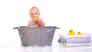 bebe in cadita de metal care face baie in spuma
