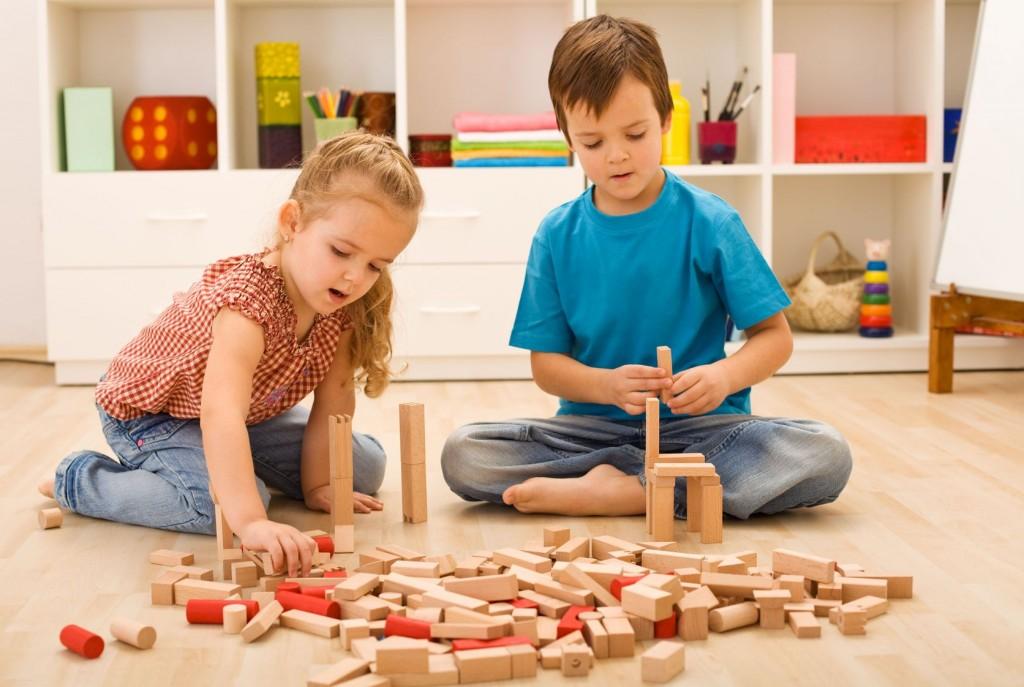 baietel si fetita care se joaca pe jos cu cuburi de lemn