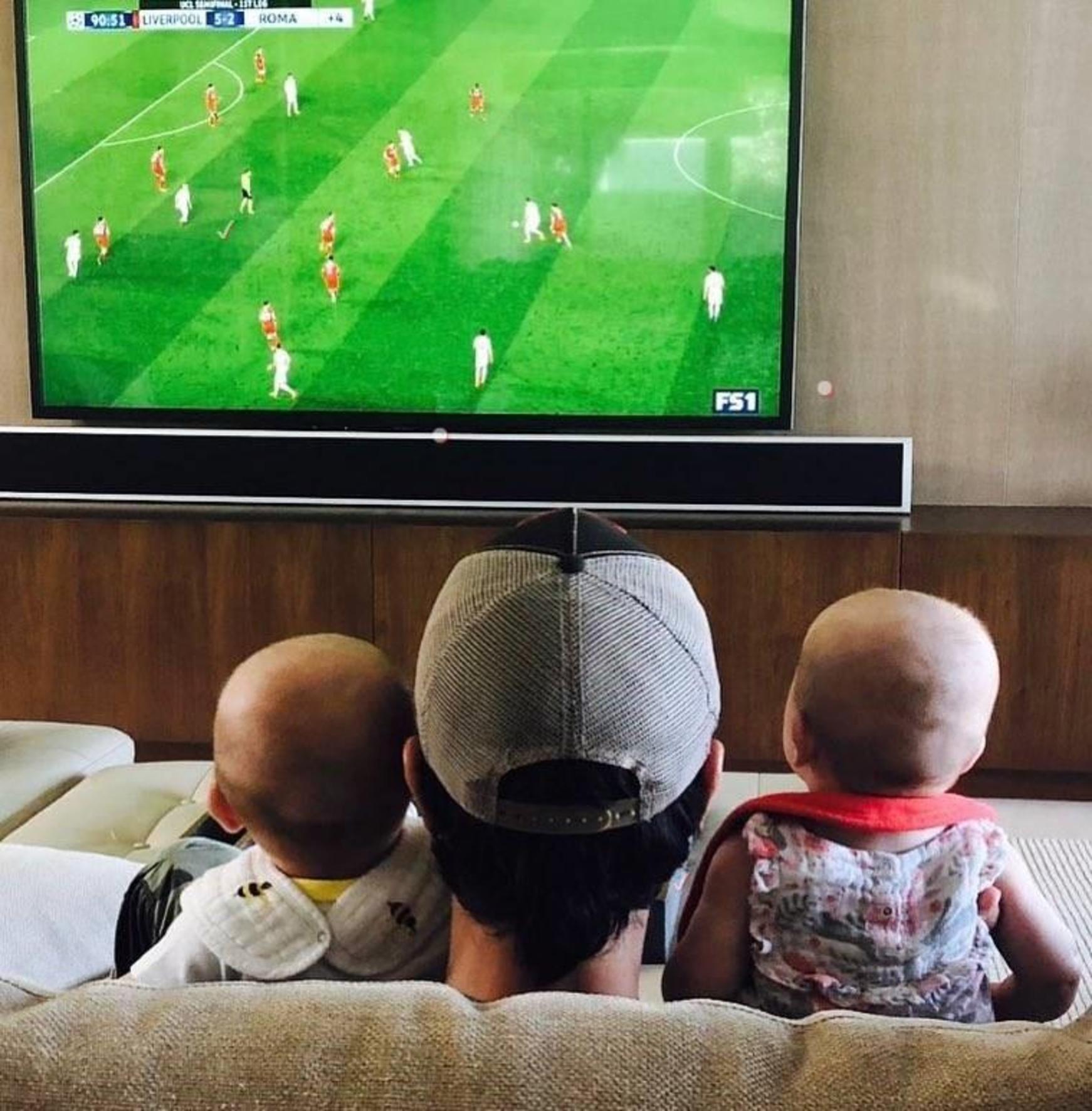 Imagine induiosatoare cu Enrique Iglesias, in care urmareste un meci cu cei doi gemeni